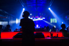 Blurred background : Club, disco DJ playing and mixing music for crowd of happy people. Nightlife, concert lights Stock Images