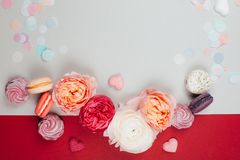 Blurred background of co-working space. Composition of macarons and flowers in grey and pink colors with confetti. Flat lay. Place for your text Royalty Free Stock Photos