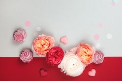 Blurred background of co-working space. Composition of macarons and flowers in grey and pink colors with confetti. Flat lay. Place for your text Stock Photos