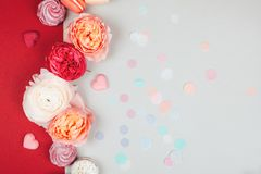 Blurred background of co-working space. Composition of macarons and flowers in grey and pink colors with confetti. Flat lay. Place for your text Royalty Free Stock Photo
