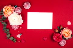 Blurred background of co-working space. Composition of macarons and flowers in grey and pink colors. Flat lay. Place for your text royalty free stock photo