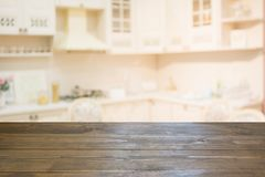 Blurred background. Empty wooden tabletop and defocused modern kitchen. Stock Image