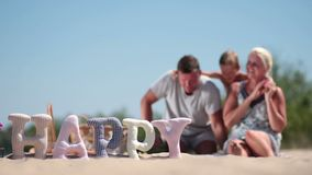 Blurred background of family having rest on beach Stock Image