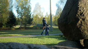 Blurred Background: the father and two sons walking in the park of large stones. A kid sitting on the Pope's neck. Autumn time stock footage