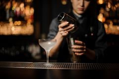 Female bartender pouring a cocktail in steel shaker on the foreground of ice glass. Blurred background of a female bartender pouring a cocktail in a steel shaker stock photos