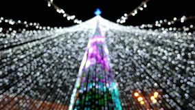 Blurred background of garlands lights on Christmas tree in the city. During the holidays stock video