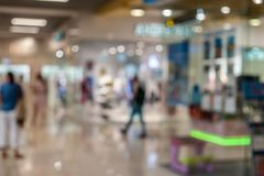 Blurred background of generic shopping mall interior neutral key with nice light bokeh royalty free stock photography