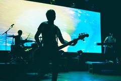 Blurred background light on rock concert. With silhouette of musicians Stock Photos