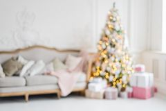 Blurred background. Luxury living room interior with sofa decorated chic Christmas tree, gifts, plaid and pillows. Stock Photos