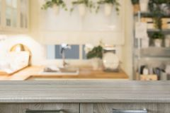 Blurred background. Modern defocused pastel kitchen with wooden tabletop and space for you. Blurred background. Modern defocused pastel kitchen with empty stock photos