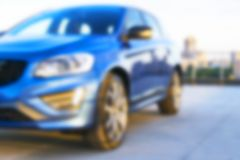 Blurred background of a A modern luxury car on the blur roof of the building. Modern car exterior details. Blurred background of a A modern luxury car on the stock photography