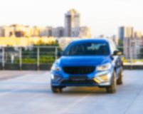 Blurred background with modern luxury car on the blur roof of the building at the sunset. Modern car exterior details. Soft. Lightning stock photography