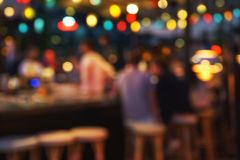 Blurred background of people sitting at restaurant, bar or night club with colorful lights bokeh. Abstract defocused blur background royalty free stock photo