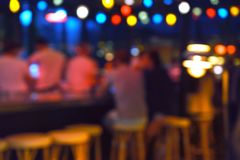 Blurred background of people sitting at restaurant, bar or night club with colorful lights bokeh. stock photo