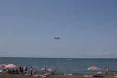 Blurred background photo of people on the beach having fun under umbrellas. Parasailing Royalty Free Stock Images