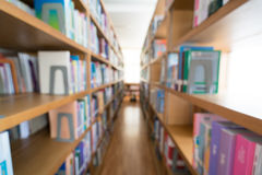 Blurred background of public library, bookshelf with books, diminishing perspective, education concept Royalty Free Stock Images