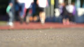 Blurred background of runners on stadium. Amateur sport footage slowmotion. Video stock footage