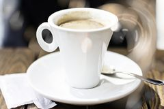 blurred background. A small white cup of coffee with milk on a wooden table with sun flares outdoors royalty free stock image