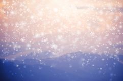 Blurred background of snow falling on blue mountain. Blurred background of snow flakes falling on blue mountain and pink sky scene Royalty Free Stock Images