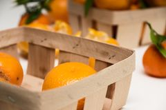 Blurred baskets of unpeeled tangerines and some purified. Blurred baskets of unpeeled, purified tangerines royalty free stock photo