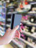 Blurred beauty and cosmetics shelves in supermarket. Female hand holding credit card with beauty and cosmetics shelves in supermarket Stock Photos