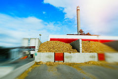 Blurred bio power plant with storage of wooden fuel biomass. Against blue sky Royalty Free Stock Photos