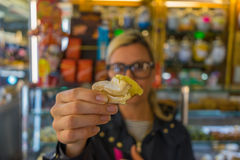 Blurred blonde woman on background holding Italian sweets with v Royalty Free Stock Image