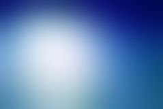 Blurred blue background with white cloudy center spot and dark gradient blue border design. Smooth blurred blue sky background with bright white sun spot and Royalty Free Stock Images