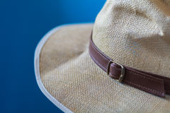 Blurred blue image of a cream hat with white fringe and brown strap Royalty Free Stock Image