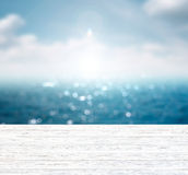 Blurred blue sea and sky with space on wooden table. stock photos