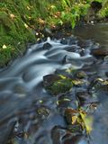 Blurred blue waves of stream running over gravel and stones.  Royalty Free Stock Photography