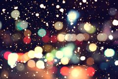 Blurred bokeh background of colorful christmas lights with snow fall stock photography