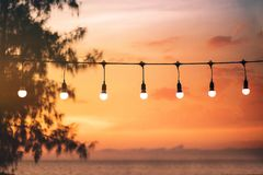Blurred light on sunset with yellow string lights decor in beach restaurant stock images
