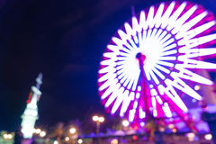 Blurred bokeh night harbor lights background with ferris wheel Royalty Free Stock Images