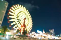Blurred bokeh night harbor lights background with ferris wheel Stock Photography