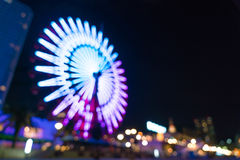 Blurred bokeh night harbor lights background with ferris wheel Stock Photos