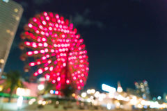 Blurred bokeh night harbor lights background with ferris wheel Stock Photo