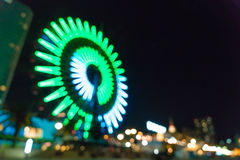 Blurred bokeh night harbor lights background with ferris wheel Stock Images