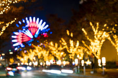 Blurred bokeh night harbor lights background with ferris wheel Royalty Free Stock Image