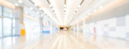 Blurred bokeh panoramic banner background of exhibition hall or convention center hallway. Business trade show event