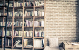 Blurred books on the shelf with brick wall in public library Stock Image