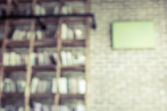 Blurred books on the shelf with brick wall in public library. In vintage color tone Stock Photos