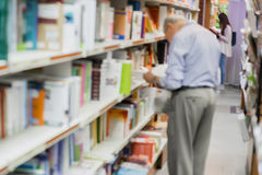 Blurred bookshelves in book store or in library. Elderly intelligent man pensioner, teacher or scientist, chooses. Blurred bookshelves in book store or in Royalty Free Stock Photo