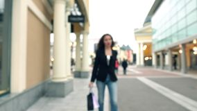 Blurred brunette girl in high heels walking with shopping bags by outlet fashion stores. 4K bokeh background video stock video footage