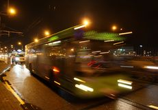 The blurred bus on the avenue in the evening. The motion of a blurred bus on the avenue in the evening stock image