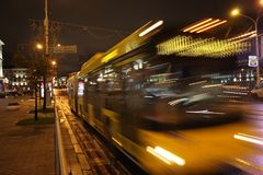 A blurred bus on the avenue. The motion of a blurred bus on the avenue in the evening royalty free stock images