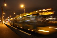 The blurred bus in the evening. The motion of a blurred bus on the avenue in the evening stock image