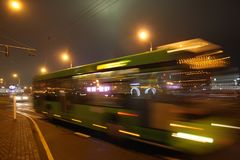 The blurred bus in the evening. The motion of a blurred bus on the avenue in the evening stock photo
