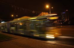 A blurred bus in the evening. The motion of a blurred bus in the street in the evening royalty free stock image