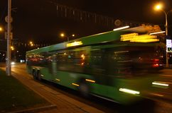 A blurred bus in the evening. The motion of a blurred bus in the street in the evening stock image